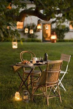 Tree-hung lanterns transform the yard for an idyllic summer dinner for two...or three or four...