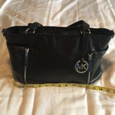"""Authentic Michael Kors leather bag. EUC! Please consider this authentic Michael Kors black real leather hand bag with silver zipper details. It measures about 18"""" wide and 12"""" tall. Bottom sits 4"""" across. It holds a lot! Will come with original shoulder strap (not pictured). The bottom is clean with no scuffs anywhere. Michael Kors Bags Shoulder Bags"""