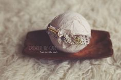 A rustic look headband, embellished with a silk flower, moss and small beads/pearlsNewborn size