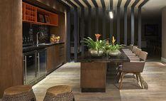 ESTILO RÚSTICO  A madeira também pode ser um acabamento marcante na cozinha. Experimente escolher cadeiras com material mais rústico, como a palhinha e insira cores em pontos estratégicos. No alto, a adega de laca vermelha e um nicho recebe utensílios que podemos usar no dia a dia.