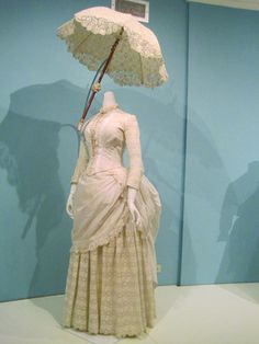 This white cotton dress is from around the late 1880s, and is an example of a typical dress that would have been worn on a seaside vacation. While this might seem like a very formal — and very elaborate — dress for beachware by today's standards, this dress would have been considered lightweight.  Kent State University Museum
