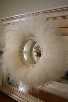 Tulle wreath, perfect for repurposing an old tutu. Note, though, that the fluffier the wreath, the more it calls for a large rhinestone brooch.