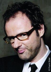 """Vince Ebert (Jahrgang 1968) studierte Physik in Würzburg. Nach dem Studium arbeitete er in einer Unternehmensberatung und in der Marktforschung, bevor er 1998 seine Karriere als Kabarettist begann. Er ist bekannt aus TV-Sendungen wie """"Mitternachtsspitzen"""", """"Ottis Schlachthof"""", dem """"Quatsch Comedy Club"""" und """"TV Total""""."""