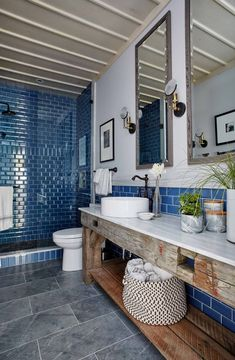 Rustic decor, royal blue subway tile shower, and blue stone floor in a modern country style bathroom by Sarah Richardson.