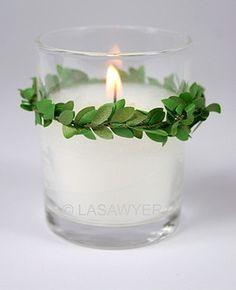 vasito de vela transparente con corona verde. vela. iluminación