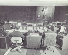 """Caption: """"AIR DEFENSE WATCH - These display screens would display signs of air attack against Canada and the United States. By pushing buttons, the NORAD battle staff members can take an electronic look at the tracks of space satellites or aircraft, which are chartered on the display by computers This is the nerve center which would give the first warning of attack, and the command post from which NORAD battle commanders would direct the defensive air battle."""""""