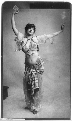 [Woman in belly-dancing costume smoking and holding package of cigarettes] c1900