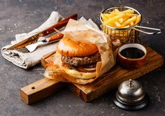 бургер - Burger with meat and French fries in basket on dark background and desk bell