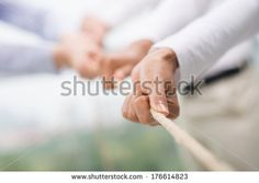 Concept image of business team using a rope as an element of the teamwork on the foreground  - stock photo