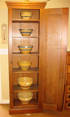 Antique chimney cupboard with yellow ware bowls.