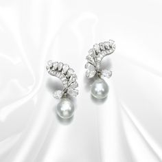 Cultured pearl and diamond earrings. Each of these scroll design earrings is set with pear-shaped and baguette diamonds, suspending cultured pearl drops.