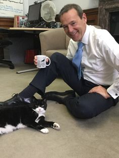"""Palmerston and Sir Simon McDonald at the Foreign Office. On the mug: """"My cat has more followers than me"""""""