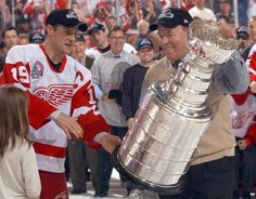 Red Wings captain Steve Yzerman hands the Stanley Cup to Scotty Bowman in 2002.