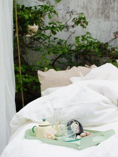 På RUNNEN trall släpar vi ut alla våra extra madrasser, kuddar och de gosigaste täcken vi har. Det blir en plats att läsa, dricka morgonte och mysa i solen - ren kärlek i naturen! URSULA kuddfodral, LINBLOMMA påslakan, ENSIDIG vas, GÄLL kopp.