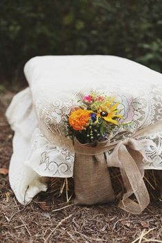 Lace and burlap covered hay bale  with aisle flowers. Love it