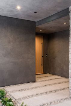 A landscaped concrete and stone path leads you to a large wooden door that stands out within its surroundings and welcomes you to the home.