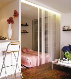 Vertical. The wall, the blinds and the shelving behind the blinds create vertical lines that create a taller, higher room.