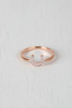 @modaonpoint This delicate ring features a high polished metal finish and a horseshoe detail embedded with rhinestones on a non-adjustable band.