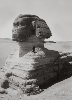 predecessors: A man standing on the Sphinx, demonstrating its size. Circa 1900s.