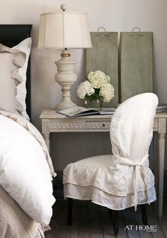 A bedside spot looks romantic with a shabby chic desk, lamp,  slipcovered chair.