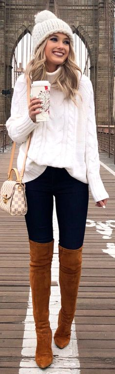 #winter #outfits white knitted jacket and blue pants with brown thigh-high boots and hat