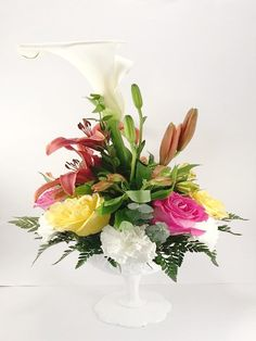 A classical Calla Lili arrangement accompanied by white and yellow roses surrounded by bright red lilies.
