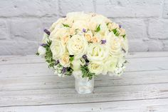 "White and cream roses accented with sprigs of lavender, create a classic and elegant bridal bouquet that can be part of your special day!  This custom wedding bouquet is 12"" in diameter and includes white ranunculus, white roses, cream roses, cream spray roses,  true lavender,  is accented with pittosporum varigated.  The edge of the bouquet is finished with grey lamb's ear leaves.  The handle is wrapped in white satin ribbon accented with a small brooch."