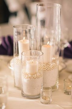 Centerpiece inspiration – Elegant wedding styling made with cylinder vases, candles, pearls and white sand | Idée de centre de table : Décoration de mariage élégante composée de vases cylindriques, bougies, perles et sable blanc