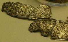 Ornate Knotwork: Gold ornaments from the burial mound at Taplow in south Buckinghamshire.    These are probably mounts from a wooden drinking cup.    From the collection at the British Museum, London.