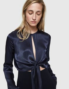 Long sleeve top from Stelen in Navy. Round neckline. Concealed back zip closure. Deep front slit. Tie-up hem. Slightly cropped.  • Satin • 53% polyester, 47% viscose • Hand wash cold