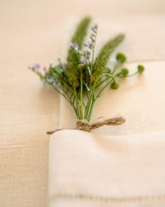 Menus at this rustic reception were tucked into linen napkins, along with a petite bunch of wildflowers and green herbs