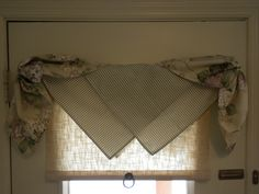 Simple window treatment - two napkins draped over cafe rod in center; napkin cinched with twist tie and hung over each end.