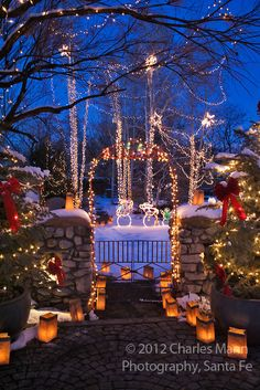 Lights adorn the trees and paper bag faralitos line the walk of a gate and yard during the annual Christmas Eve celebration of lights on Canyon Road in Santa Fe, New Mexico.