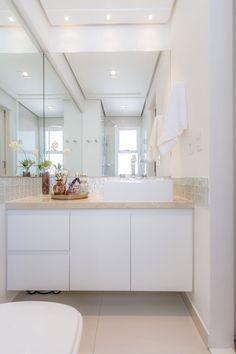 """Banheiro compacto e charmoso: """"trabalhamos uma faixa de pastilhas de vidro em todo o perímetro do banheiro. Fizemos também uma nova bancada com cuba sobreposta, abusamos dos espelhos em duas paredes e fizemos a composição com porcelanato neutro no piso e na área de box"""", explica."""