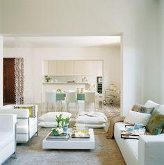 Salón blanco abierto al comedor y la cocina con sofá y dos butacas_ 00212898