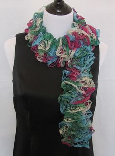 Christmas hand knitted ruffle scarf in jewel tones of magenta, green, blue and silver. Has silver thread thru out that makes it sparkle. #Christmas    #sparkly