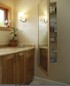 Built in shelves for small bathroom w mirror to cover and reflect light.