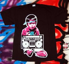 (LAST ONE LEFT) The Baby Boomer Tee is OxDx's first public print. Traditional Navajo baby jammin out on his ghetto blaster has become a quick classic. The photo also depicts the turquoise OxDx logo on the upper back of the tee. Pay your homage to good music and rock this tee.