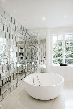 Husets masterbadeværelse har masser af plads. De smukke facetslebne spejlfliser danner et dekorativt vægmaleri, som kan nydes, når man sidder i det runde badekar fra Copenhagen Bath.