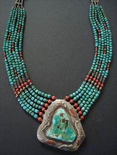 Nepal | asymetrical large turquoise pendant surrounded with etched hammered silver embedded with coral. Six strands of turquoise beads graduating in size, coral & brass spacer beads  Finished with silver hook clasp