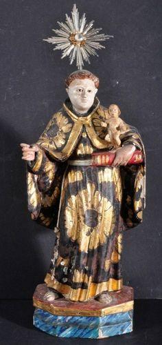 Imagem em madeira esculpida, entalhada e dourada, representando Santo Antonio com o Menino Jesus de pé, sobre um livro. Resplendor de prata, olhos de vidro, sobre uma base hexagonal. Medindo 36 cm de altura. Portugal. Séc XIX. Base R$3.000,00. Não vendido.