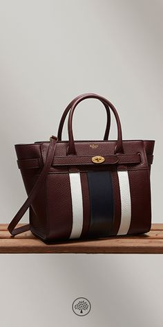 Shop the Small Zipped Bayswater in Oxblood, White & Midnight College Stripe Small Classic Grain Leather at Mulberry.com. The Small Zipped Bayswater is a sophisticated tote adopting the clean and structured aesthetic of the iconic Bayswater bag. The belt detailing finished with the Postman's lock gives this style an elegant and fashionable look. For the Summer '17 Collection, the Small Zipped Bayswater reinterprets the Oxbridge college stripes - one of the key inspirations behind the…