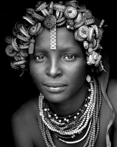 Daasanach Tribe Girl, Omorate,Ethiopia by Eric Lafforgue  Apparently, the Daasanach people collect Coca Cola/beer caps from bars to make head dresses.