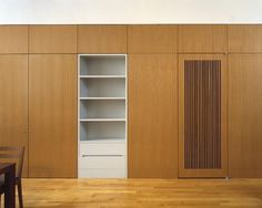 Mercer Street Loft - Rift Oak Millwork Photo: Eduard Hueber  Oak Veneer modern cabinetry with inset white niche with selving color change and laundry or av closet door with cut vents