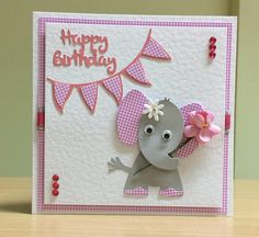 A lovely birthday card handmade in Wakefield, West Yorkshire. It features a cute elephant with a white flower on her ear. The elephant is holding a pink flower and has pink and white checked ears. The card has the greeting Happy Birthday, has pink and white checked bunting, is