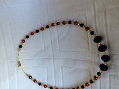 This 14in long necklace is made of metallic red and black beads with gold…