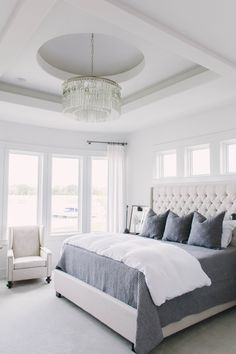 Neutral master bedroom with gray and blue accents and lake views. love the upholstered headboard and dramatic crystal chandelier. master bedroom 2016 Omaha Street of Dreams : Home Hamptons Bedroom, Coastal Master Bedroom, Dream Master Bedroom, Romantic Master Bedroom, Coastal Bedrooms, Master Bedroom Design, Beautiful Bedrooms, Home Decor Bedroom, Modern Bedroom