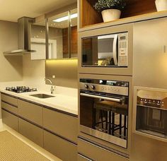 Cozinha bege, microondas e fogao altos e embutidos