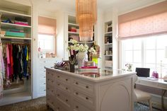 Alice Lane Home Collection   Rachel Parcell - Pink Peonies office/closet   pink chandelier, closet organization,  walk-in closet, leopard carpet, pink roman shades, custom island, built-in cabinetry, pink walls, white shelving, fashion