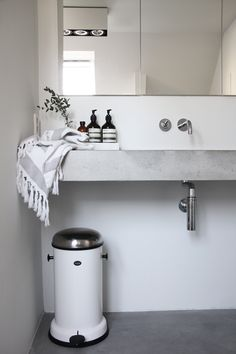 Love the simple, clean lines of this design stark white paint elongated mirror concrete counter modern fixtures amp; futuristic trash container would make this space easy to keep clean amp; Decor, Gray And White Bathroom, Interior, Home, Bathroom Styling, Concrete Floors, Bathroom, White Bathroom, Bathroom Inspiration